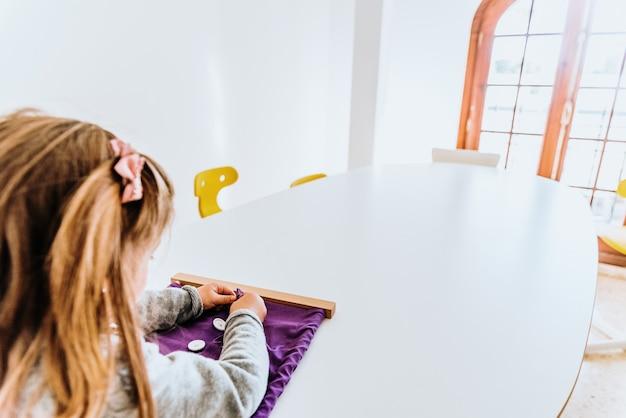 Fille qui boutonne un cadre de montessori pour développer la dextérité de ses doigts. Photo Premium