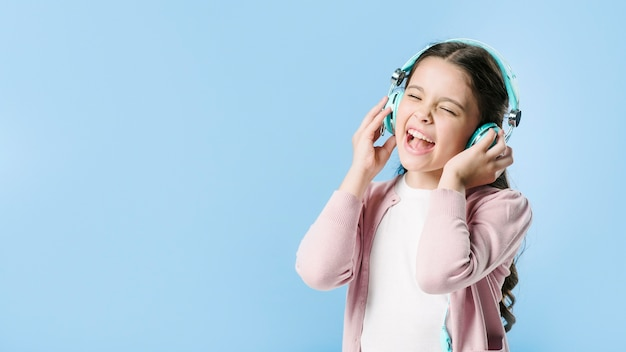 Fille qui chante dans les écouteurs en studio Photo gratuit