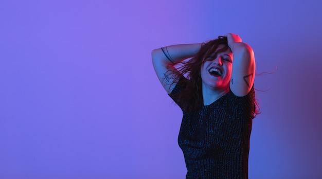 Fille qui danse et s'amuse à la fête. lumière colorée, studio tourné, surface Photo Premium