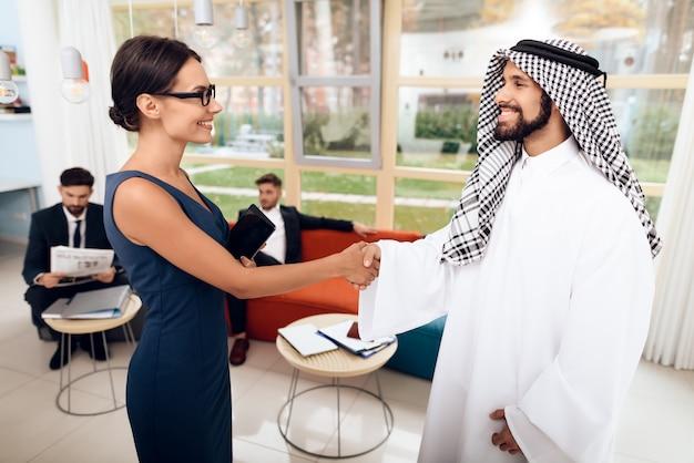 Fille qui parle avec des hommes d'affaires arabes sur une entreprise. Photo Premium