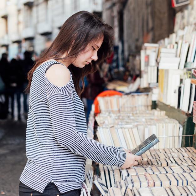 Fille à la recherche de vieux livres Photo gratuit