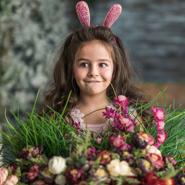 Fille réfléchie dans les oreilles de lapin avec des fleurs Photo gratuit
