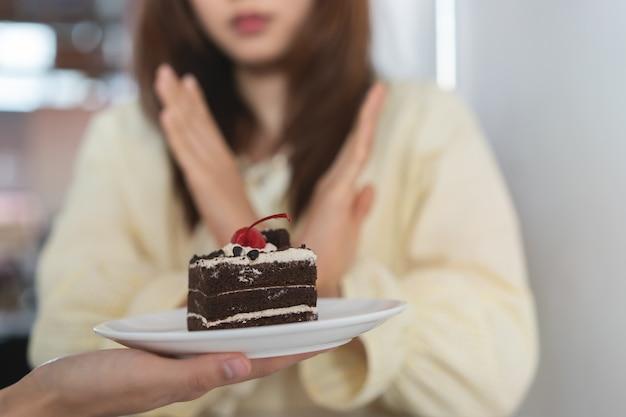 Fille refuser de manger des bonbons ou des gâteaux pendant le régime. Photo Premium