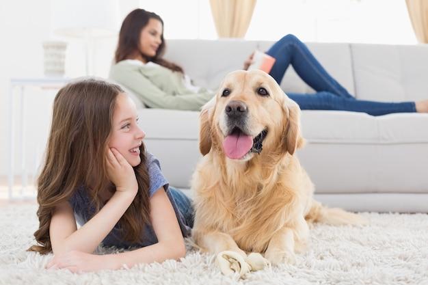 Fille regardant chien en position couchée sur le tapis Photo Premium