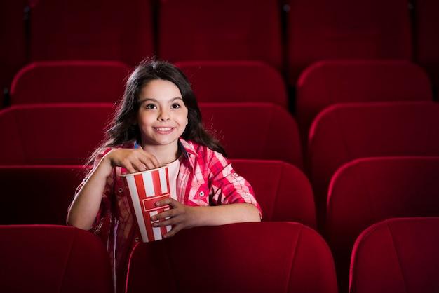 Fille regardant un film au cinéma Photo gratuit