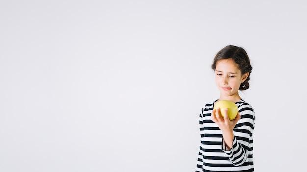 Fille regardant la pomme avec dégoût Photo gratuit