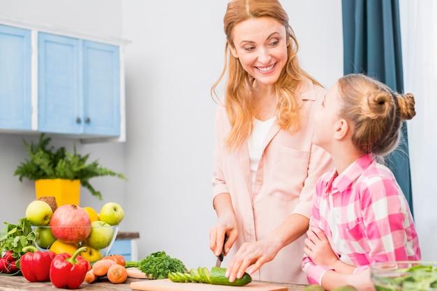 Fille regardant sa mère souriante coupe le concombre avec un couteau dans la cuisine Photo gratuit