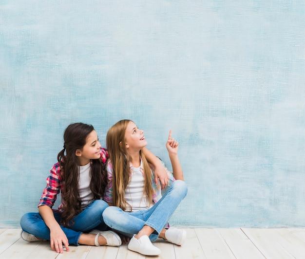 Fille regardant son ami souriant, pointant le doigt vers le haut sur fond bleu Photo gratuit