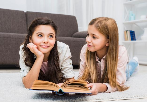 Fille Regardant Son Amie Réfléchie En Lisant Un Livre Dans Le Salon Photo gratuit