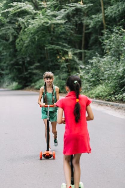 Fille regardant son amie trottinette sur route Photo gratuit
