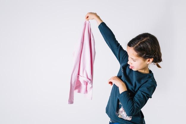 Fille regardant le tissu avec dégoût Photo gratuit