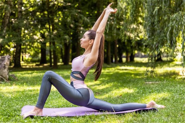 Fille De Remise En Forme, Faire Des Exercices Sur La Pelouse Dans Un Parc Photo gratuit