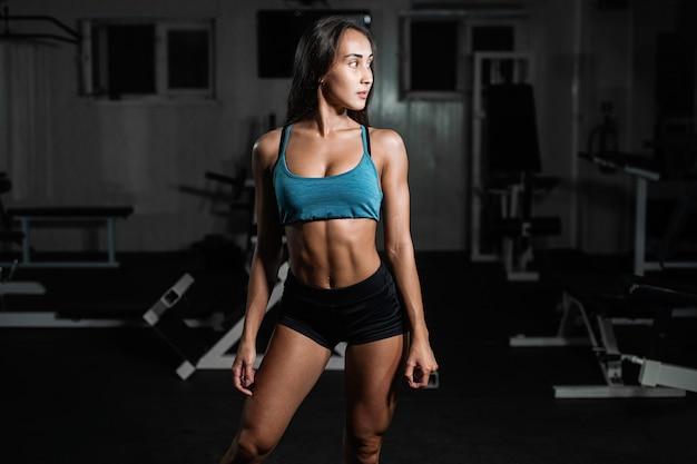 Fille de remise en forme avec haltère, femme posant dans une salle de sport Photo Premium