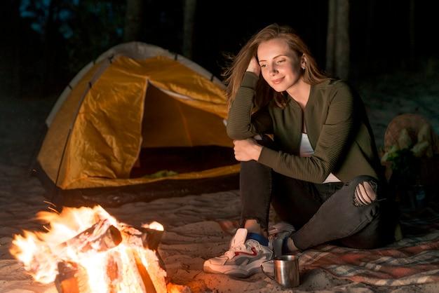 Fille rêveuse regardant le feu de camp Photo gratuit
