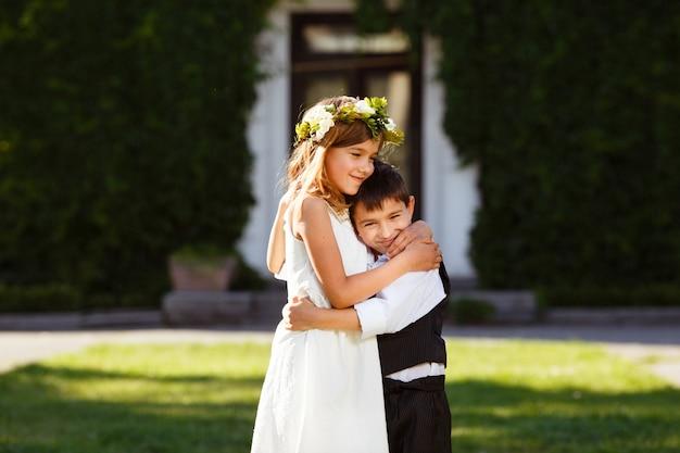 Une Fille En Robe Blanche Embrasse Un Garçon Dans Un Costume à La Mode. Photo Premium
