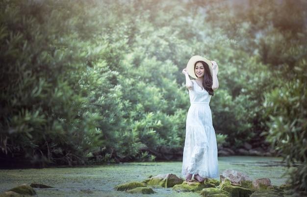 Une fille en robe blanche se dresse dans la forêt. Photo Premium