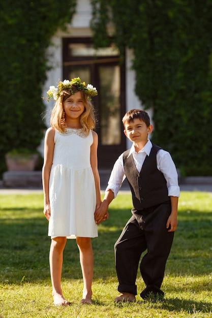 Une Fille En Robe Blanche Tient La Main D'un Garçon Dans Un Costume à La Mode Photo Premium
