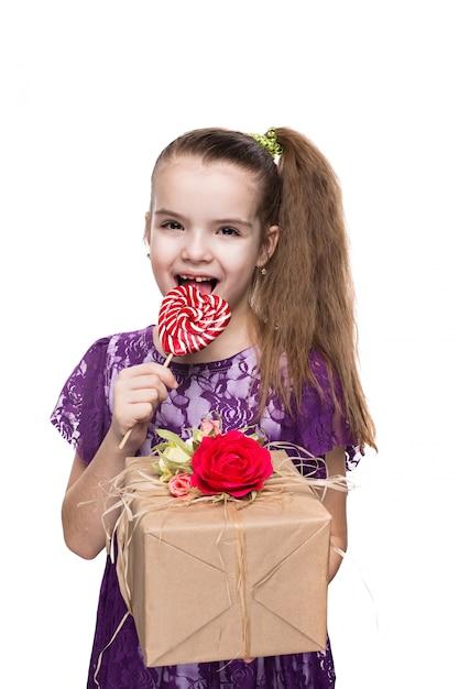 Fille en robe de dentelle pourpre tenant une boîte avec un cadeau décoré de fleurs. Photo Premium