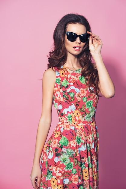 Fille En Robe à Fleurs Et Lunettes De Soleil Posant Photo Premium
