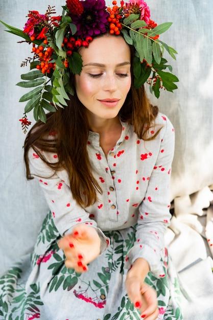 Fille en robe en lin. avec une guirlande de fleurs sur sa tête. Photo gratuit