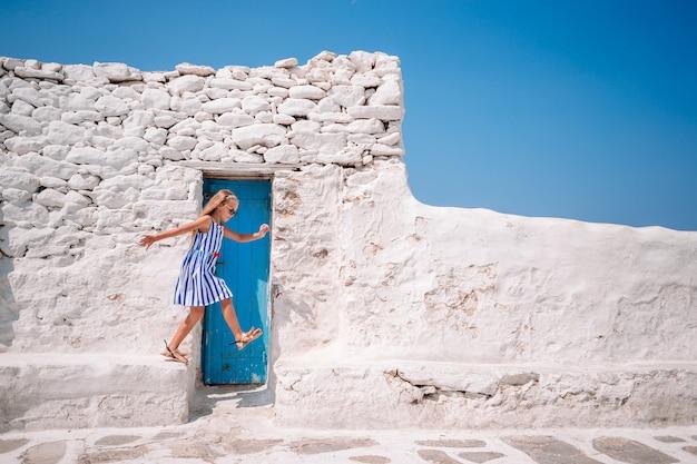 Fille en robes bleues s'amusant en plein air dans les rues de mykonos Photo Premium