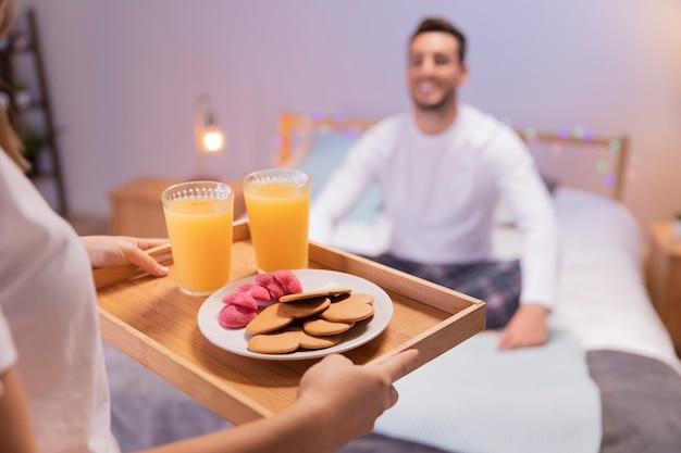 Fille romantique apporte le petit déjeuner à son mari Photo gratuit
