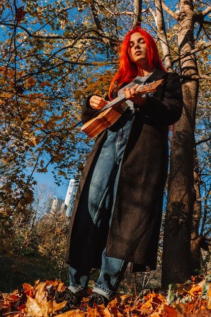 Fille Rousse Aux Cheveux Longs Joue Sur Le Ukulélé Dans Le Parc. Photo Premium