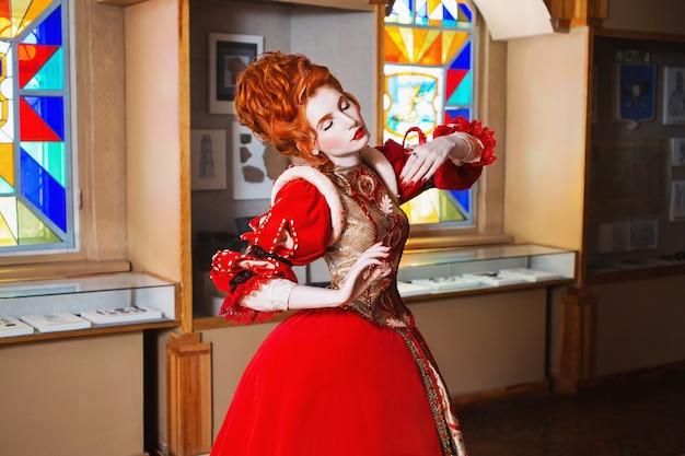 Fille Rousse Aux Yeux Bleus En Robe Rouge. Reine Avec Une Coiffure Haute. Image Vintage. Une Femme à La Peau Pâle Photo Premium