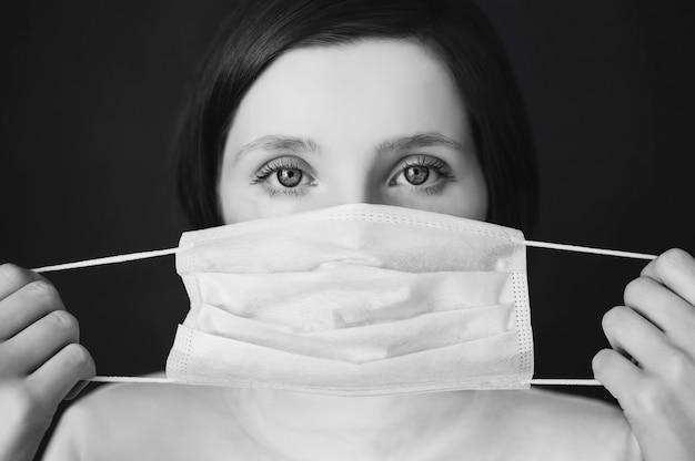 Fille Rousse Avec Un Masque Médical Sur Un Rouge, Femme Médecin, Européen, Masque Médical à La Main, La Jeune Fille Dans Un Col Roulé Blanc Photo Premium