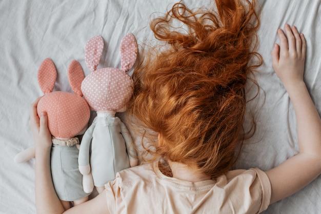 Fille Rousse Avec Des Poupées Sur Le Lit. Photo Premium