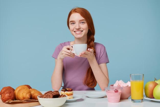 Fille Rousse Souriante Aux Cheveux Tressés Assis à Une Table, Tient Une Tasse Blanche Avec Une Délicieuse Boisson Dans Les Mains Photo gratuit