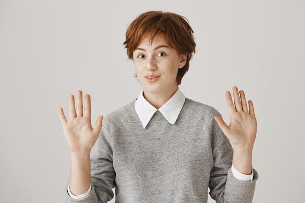 Fille Rousse Souriante Maladroite Avec Coupe De Cheveux Courte Posant Contre Le Mur Blanc Photo gratuit