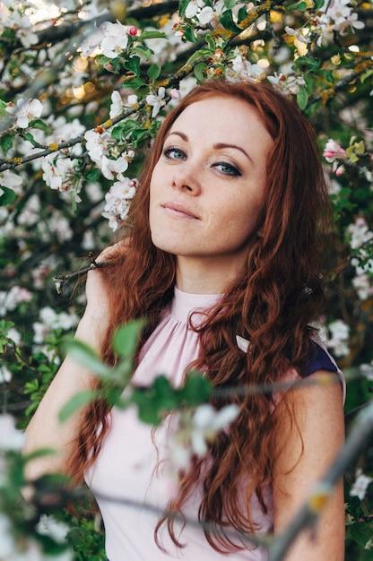 Fille rousse avec des taches de rousseur près du pommier Photo Premium