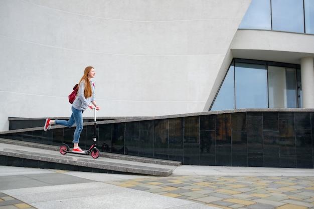 Fille rousse vêtue d'un sweat à capuche gris, d'un jean bleu et de baskets rouges à cheval sur le trottinette près d'un bâtiment moderne Photo Premium