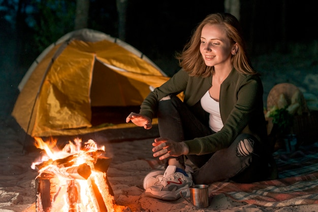 Fille s'échauffant près d'un feu de camp Photo gratuit