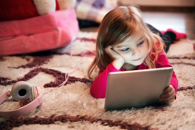 Fille s'ennuie avec tablette sur un tapis Photo gratuit