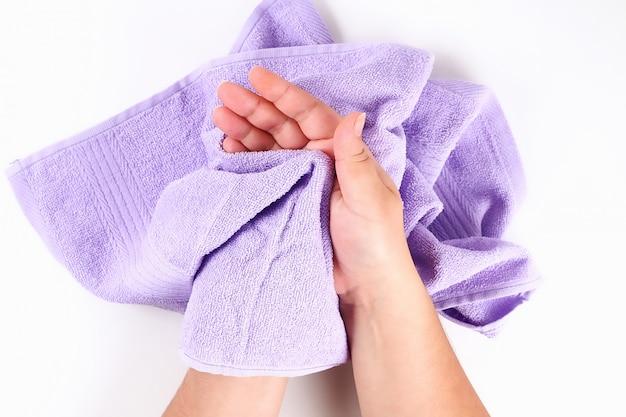 Fille s'essuie les mains avec une serviette violette sur blanc. vue de dessus. Photo Premium