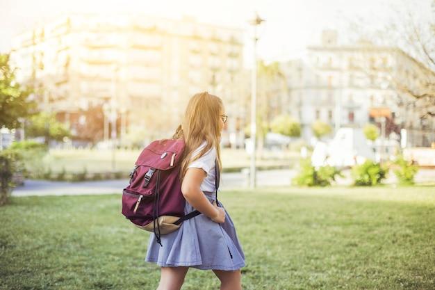 Fille avec sac à dos marchant sur la pelouse en ville Photo gratuit
