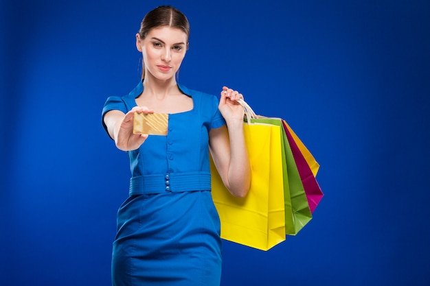 Fille avec des sacs et une carte de crédit dans les mains Photo Premium