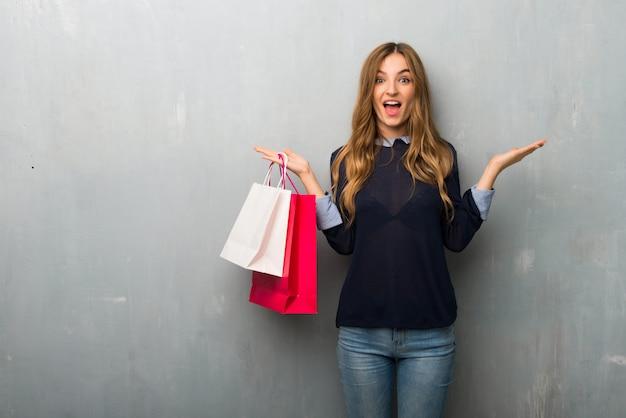 Fille avec des sacs à provisions avec une expression faciale surprise et choquée Photo Premium
