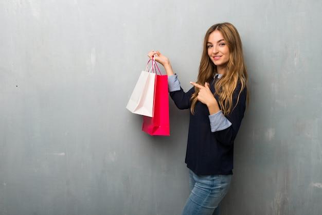 Fille avec des sacs à provisions pointant le doigt sur le côté en position latérale Photo Premium