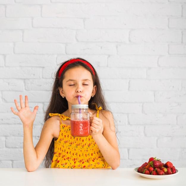 Fille satisfaite, boire des smoothies à la fraise en pot Photo gratuit