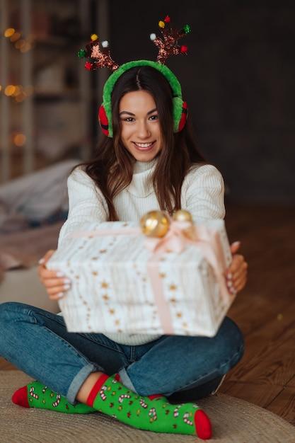 Fille Se Bouchent Avec Un Cadeau Souriant à La Caméra. Elle Porte Des Bois De Noël. Photo gratuit