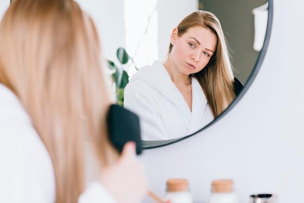 Fille se brosser les cheveux à la salle de bain Photo gratuit