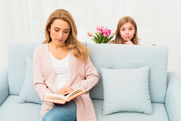 Fille se cachant derrière un canapé avec sa mère Photo gratuit