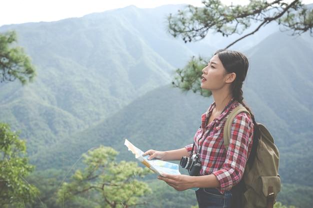 Une fille se leva pour voir la carte au sommet d'une colline dans une forêt tropicale avec des sacs à dos dans la forêt. aventure, randonnée. Photo gratuit