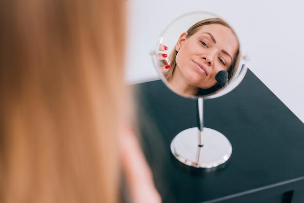 Fille se maquillant à la salle de bain Photo gratuit