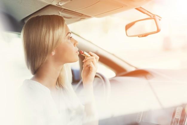 Fille se peint les lèvres au volant Photo Premium