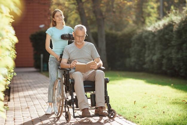 La fille se tient à côté de la poussette du vieil homme. Photo Premium