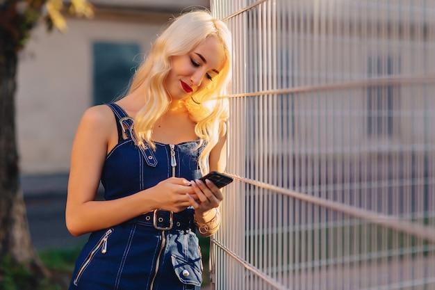 Fille séduisante blonde émotive à lunettes de soleil avec téléphone en été soleil urbain Photo Premium